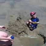 Tristan fait un château de sable.